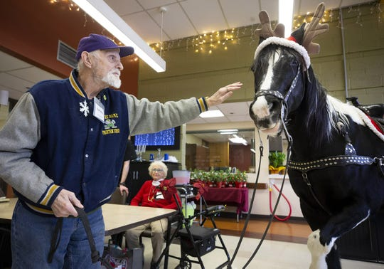 Thomas Weslowski, pets Dusty, during a holiday program at Desert Mission Adult Day Health Center in Phoenix on Dec. 13, 2019.