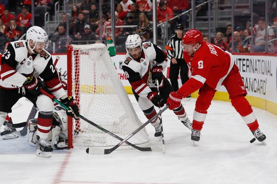 Detroit Red Wings left wing Justin Abdelkader (8) loses control the puck as Arizona Coyotes defenseman Oliver Ekman-Larsson (23) and center Nick Schmaltz (8) defend during the first period of an NHL hockey game, Sunday, Dec. 22, 2019, in Detroit. (AP Photo/Carlos Osorio)