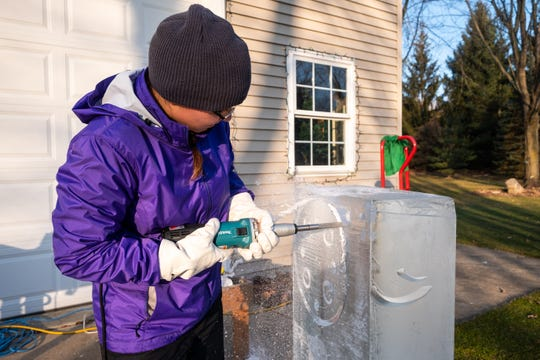 Katlin Pfropper uses a die grinder to carve a fishing reel out of a block of ice Saturday, Dec. 21, 2019, at her family's home in Lenox.