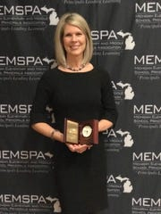 Therese Damman receives her Michigan Elementary and Middle School Principals Association Region 6 Outstanding Principal of the Year award.
