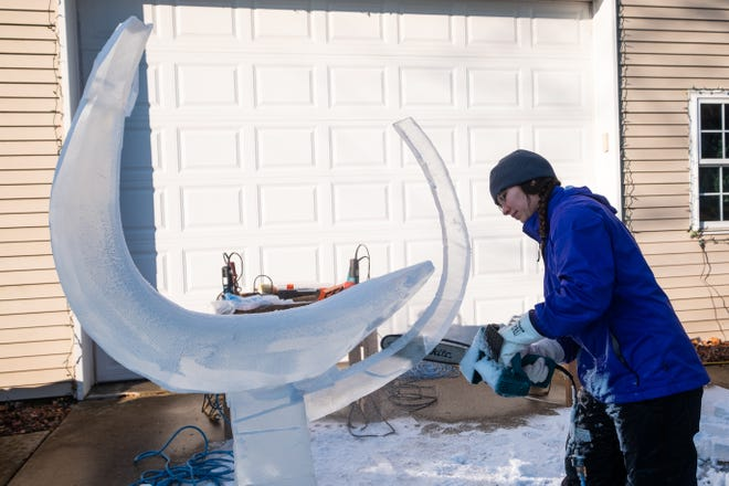 Katlin Pfropper uses a chainsaw to shape her ice sculpture Saturday, Dec. 21, 2019, at her family's home in Lenox. Pfropper was practicing her sculpture for this year's competition in Frankenmuth.