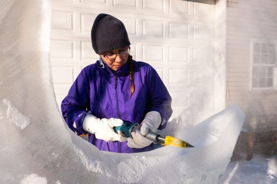 "Katlin Pfropper uses an ""everything bit"" on a large die grinder to shape her ice sculpture Saturday, Dec. 21, 2019, at her family's home in Lenox. The tool is useful for shaping and detail work, said Pfropper, who was practicing her sculpture for this year's competition in Frankenmuth."