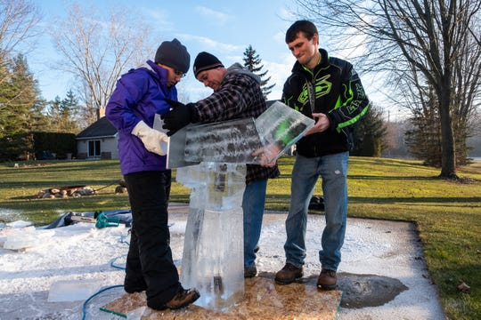 Katlin Pfropper, left, with the help of her father Tom Pfropper, center, and boyfriend Jacob Hill, fuses ice blocks together before carving them Saturday, Dec. 21, 2019, at her family's home in Lenox. Pfropper was practicing her sculpture for this year's competition in Frankenmuth.