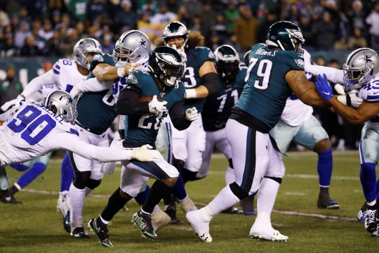 Dallas Cowboys defensive end Demarcus Lawrence (90) tries to stop Philadelphia Eagles running back Miles Sanders, center, during the first half of an NFL football game Sunday, Dec. 22, 2019, in Philadelphia. (AP Photo/Chris Szagola)