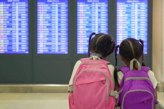Children checking their flight at information board in international airport terminal. (Dreamstime/TNS)
