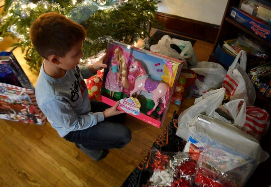 Maximus Morales, 9, a fourth grade student at East York Elementary, sorts through gifts he and his family purchased for area homeless children, Monday, December 23, 2019. John A. Pavoncello photo