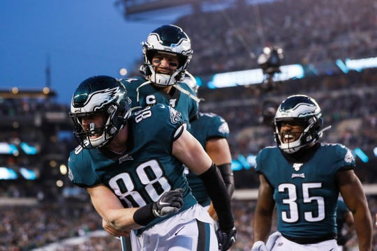 Philadelphia Eagles tight end Dallas Goedert (88) celebrates a touchdown with Carson Wentz, top, and Boston Scott (35) during the first half of an NFL football game against the Dallas Cowboys Sunday, Dec. 22, 2019, in Philadelphia. (AP Photo/Michael Perez)