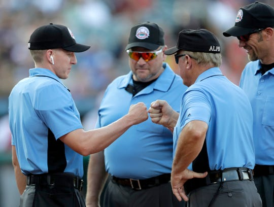 FILE - In this July 10, 2019, file photo, home plate umpire Brian deBrauwere, left, huddles with officials while wearing an earpiece connected to a ball and strikes calling system before the Atlantic League All-Star minor league baseball game in York, Pa. (AP Photo/Julio Cortez)