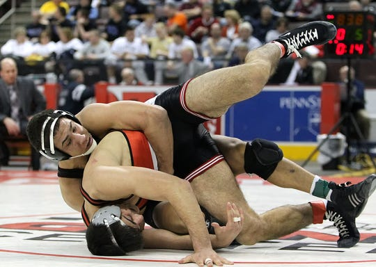Governor Mifflin's Jan Johnson, top, takes down Parkland's Nezar Haddad during a 195-pound finals match in the PIAA 3A wrestling championships in 2014. Johnson had scholarship offers for three sports, but he wanted to go to Penn State, where he walked on to the football team and eventually become a starter.