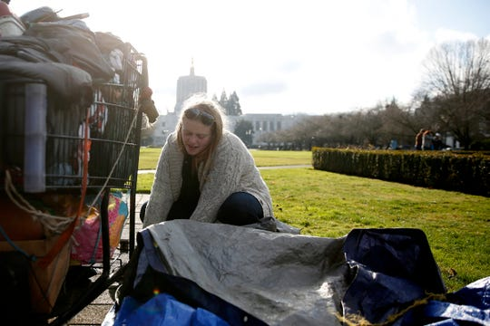 Anna Kistner, 24, takes down a site for another person after being told to leave by state officials after about 25 homeless people camped on the Oregon State Capitol Mall in Salem on Dec. 23, 2019.