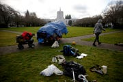 People clear out tents and tarps after being told to the Oregon State Capitol Mall in Salem on Dec. 23, 2019. A no-camping ordinance on city property went into effect last week.