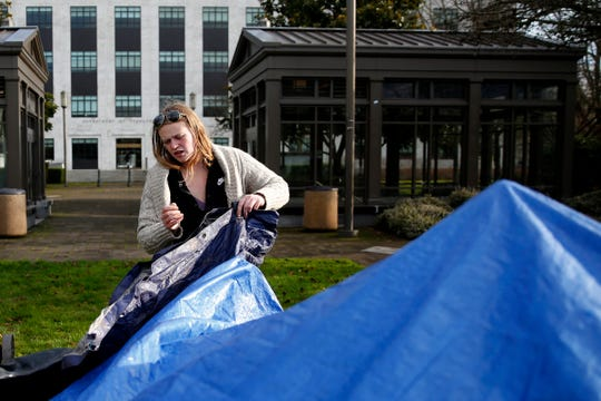 Annastasia Kistner takes down a site for another person after being told to leave by state officials after about 25 homeless people camped on the Oregon State Capitol Mall in Salem on Dec. 23, 2019.