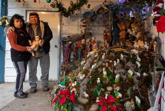 Beatriz Mendez Garcia and her husband Baltazar Garcia stand next to a large nativity scene that they put up every year for their annual posada.