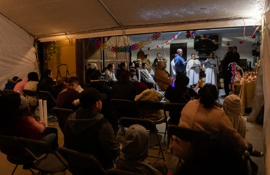 People sit down during a posada that is being hosted by the Martinez family on Dec. 16, 2019.