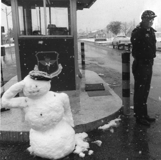 A snowman salutes residents of Goodfellow Air Force Base as Sgt. Todd Brown waves cars into the base in this archived photo from Dec. 11, 1986.