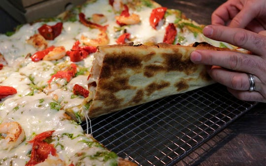Prohibition Bistro's Avni Latifi holds up a cross section of the special Roman Pizza after cooking, Tuesday, December 17, 2019, in Sheboygan, Wis. Latifi describes the dough to be pastry like rather than like normal pizza dough.