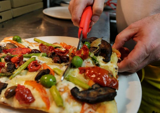 Prohibition Bistro's Avni Latifi cuts apart a finished Roman Pizza, Tuesday, December 17, 2019, in Sheboygan, Wis.