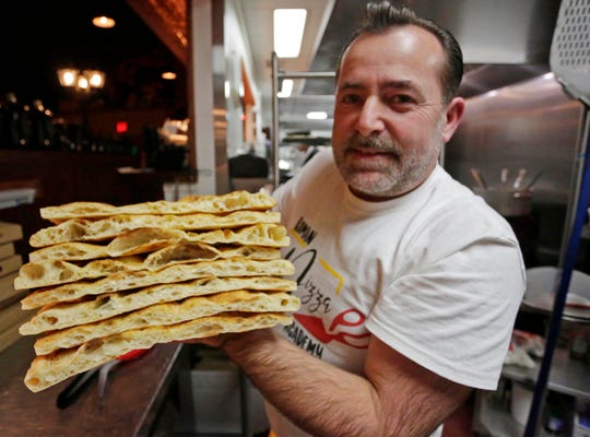 Avni Latifi holds a stack of Roma-style pizza crusts at Harry's Prohibition Bistro,  in Sheboygan.  Latifi says the special  dough, when done correctly, should have a nearly pastry like consistency.
