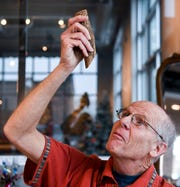 """Augustana biology professor Craig Spencer holds part of the """"bejuco de agua"""" plant on Monday, Dec. 16, 2019 at 421 N. Phillips Ave. in Sioux Falls. Through the Guatemala Maya Cross Project the plant is harvested in order to create handmade items. The proceeds from the sales are given to the artisans in Guatemala in an effort to reduce the rate of poverty."""