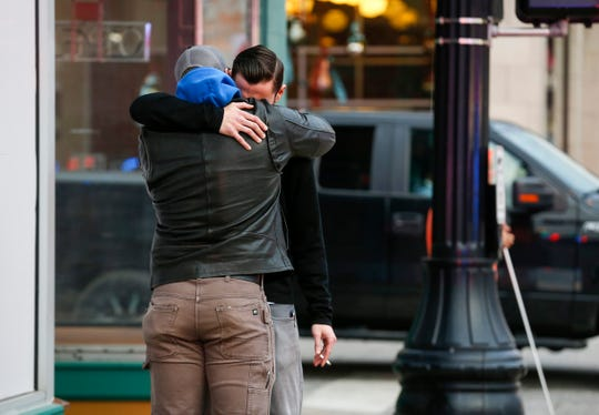Two men hug each other as firefighters and EMT's treat a possible opioid overdose at a downtown business on Thursday, Dec. 5, 2019.