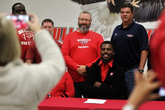 Wakulla senior linebacker Keyshawn Greene, a four-star prospect and a U.S. Army All-American, takes a photo with his head coach Scott Klees and assistants after signing with Nebraska. Greene was also named the 2019 All-Big Bend Defensive Player of the Year after recording 147 tackles for the 13-1 War Eagles.