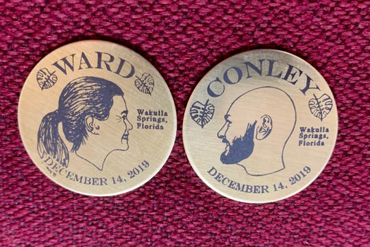 Profile illustrations of Darcy Ward and Jeff (Conley) Ward adorn brass coins flipped at their wedding to determine which last name they'd share -- hers, or his.