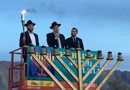 State Rep. Cesar Blanco, on the right, is the honored guest at lighting of the first candle of the menorah for Hanukkah.