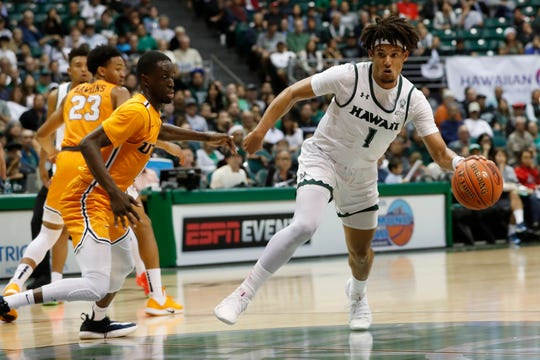 Hawaii guard Drew Buggs (1) gets around UTEP guard Souley Boum (0) during the first half of an NCAA college basketball game Sunday, Dec. 22, 2019, in Honolulu. (AP Photo/Marco Garcia)