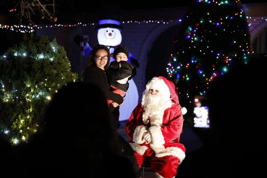David Franklin, dressed as Santa Claus, poses for a photo with a parent and their child while touring the Eastridge neighborhood.