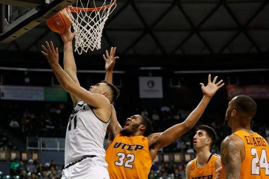 Hawaii center Mate Colina (11) gets around UTEP forward Efe Odigie (32) during the first half of an NCAA college basketball game Sunday, Dec. 22, 2019, in Honolulu. (AP Photo/Marco Garcia)