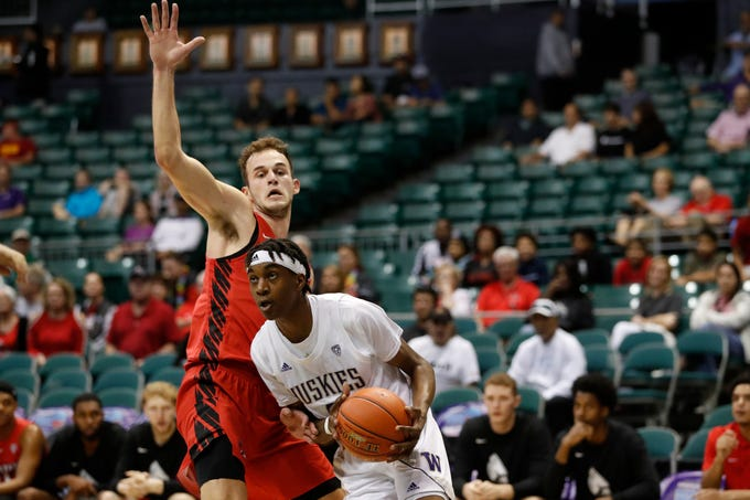 Washington forward Miryne Thomas (0) gets past Ball State forward Kyle Mallers (14) during the first half of an NCAA college basketball game Sunday, Dec. 22, 2019, in Honolulu. (AP Photo/Marco Garcia)