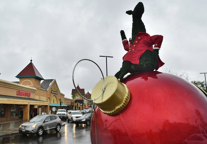 Last-minute Christmas shoppers battle wet weather and traffic at the Tulare Outlets on Dec. 23, 2019.