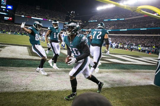 Eagles' Miles Sanders (26) celebrates with his teammates after scoring a touchdown Sunday night against the Cowboys. The Eagles defeated the Cowboys 17-9.