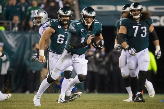 Eagles' Carson Wentz (11) runs the ball under pressure Sunday night against the Cowboys. The Eagles defeated the Cowboys 17-9.