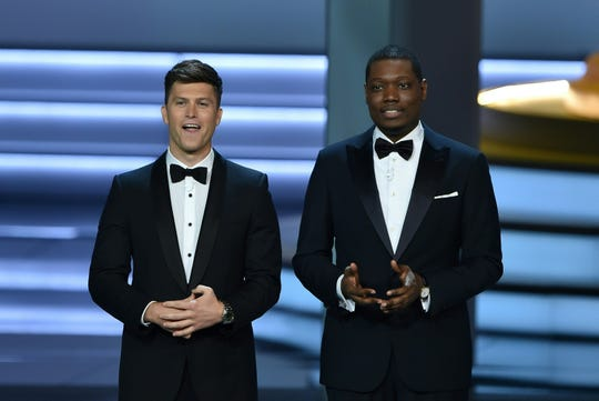 Colin Jost (left) and Michael Che speak onstage during the 70th Emmy Awards at the Microsoft Theatre in Los Angeles on Sept. 17, 2018.