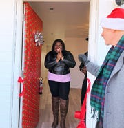 Davian Higgins-Reeves (left) reacts to the new New Castle-area home she'll be living in. Habitat for Humanity of New Castle County CEO Kevin L. Smith is outside.