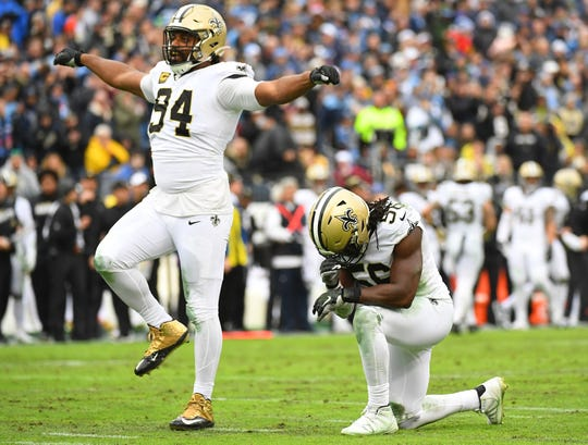 New Orleans Saints defensive end Cameron Jordan (94) and outside linebacker Demario Davis (56) celebrate after a sack during the first half against the Tennessee Titans at Nissan Stadium.