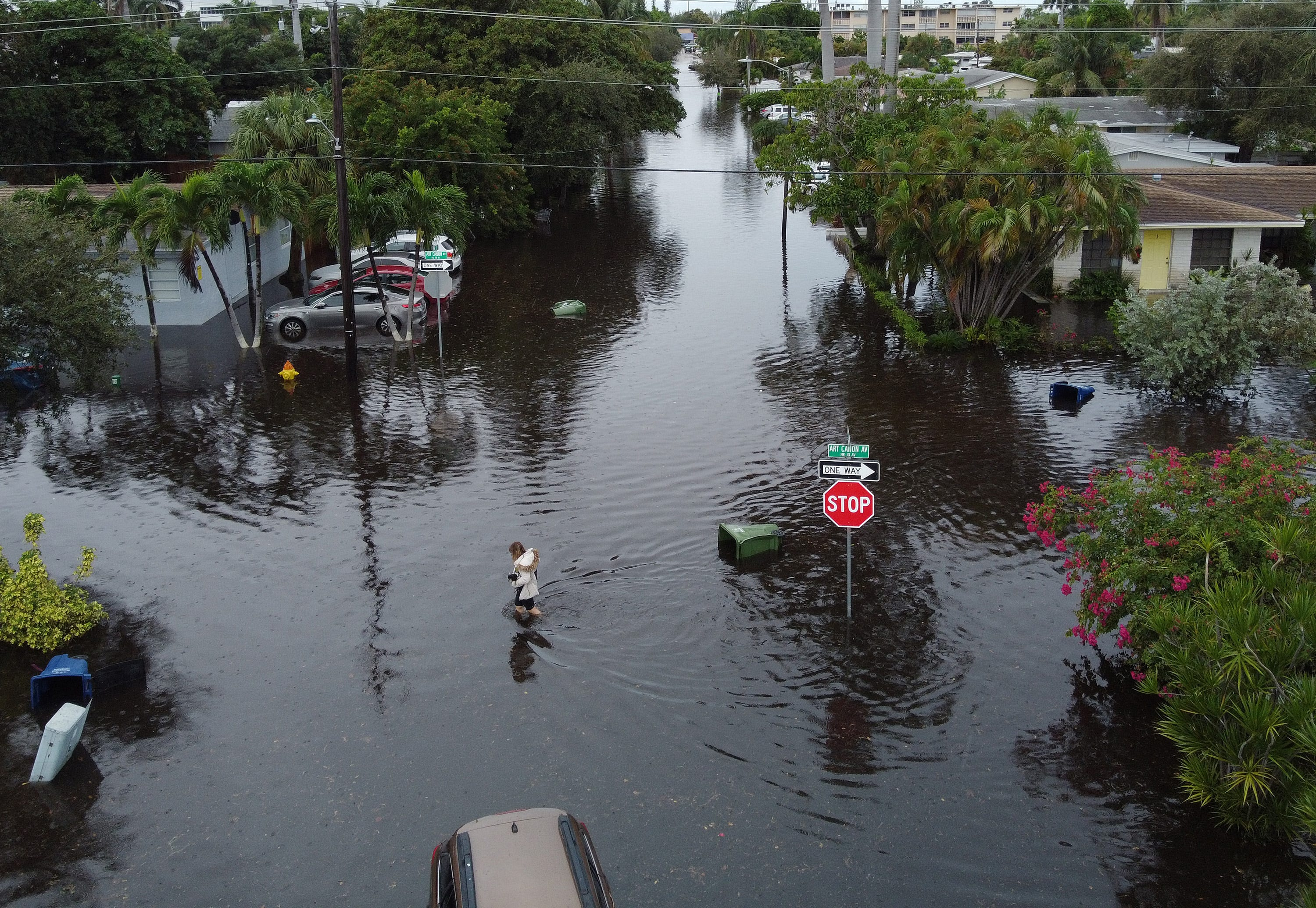 An aerial view from a drone shows a woman crossing a street inundated with flood water on Dec. 23, 2019 in Hallandale, Fla. The area received up to 12 inches of rain during an overnight storm that hit the area causing flooding that even forced Fort Lauderdale-Hollywood International Airport to shut down flight operations early Monday morning.