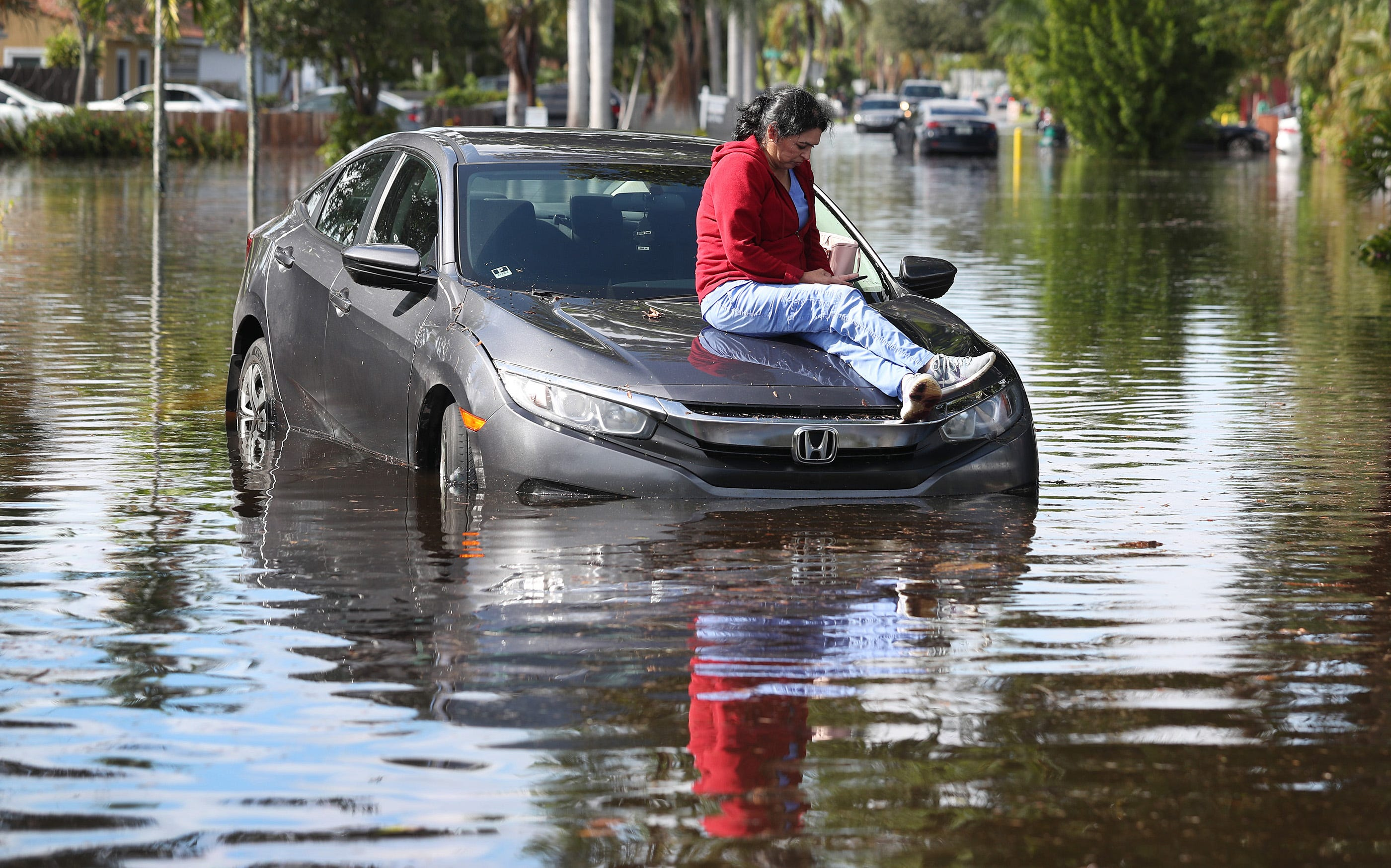 Stephanie Soto sits on the hood of her car after it stalled in flood waters as she was driving on Dec. 23, 2019 in Hollywood, Fla. The area received up to 12 inches of rain during an overnight storm that hit the area causing flooding that even forced Fort Lauderdale-Hollywood International Airport to shut down flight operations early Monday morning.
