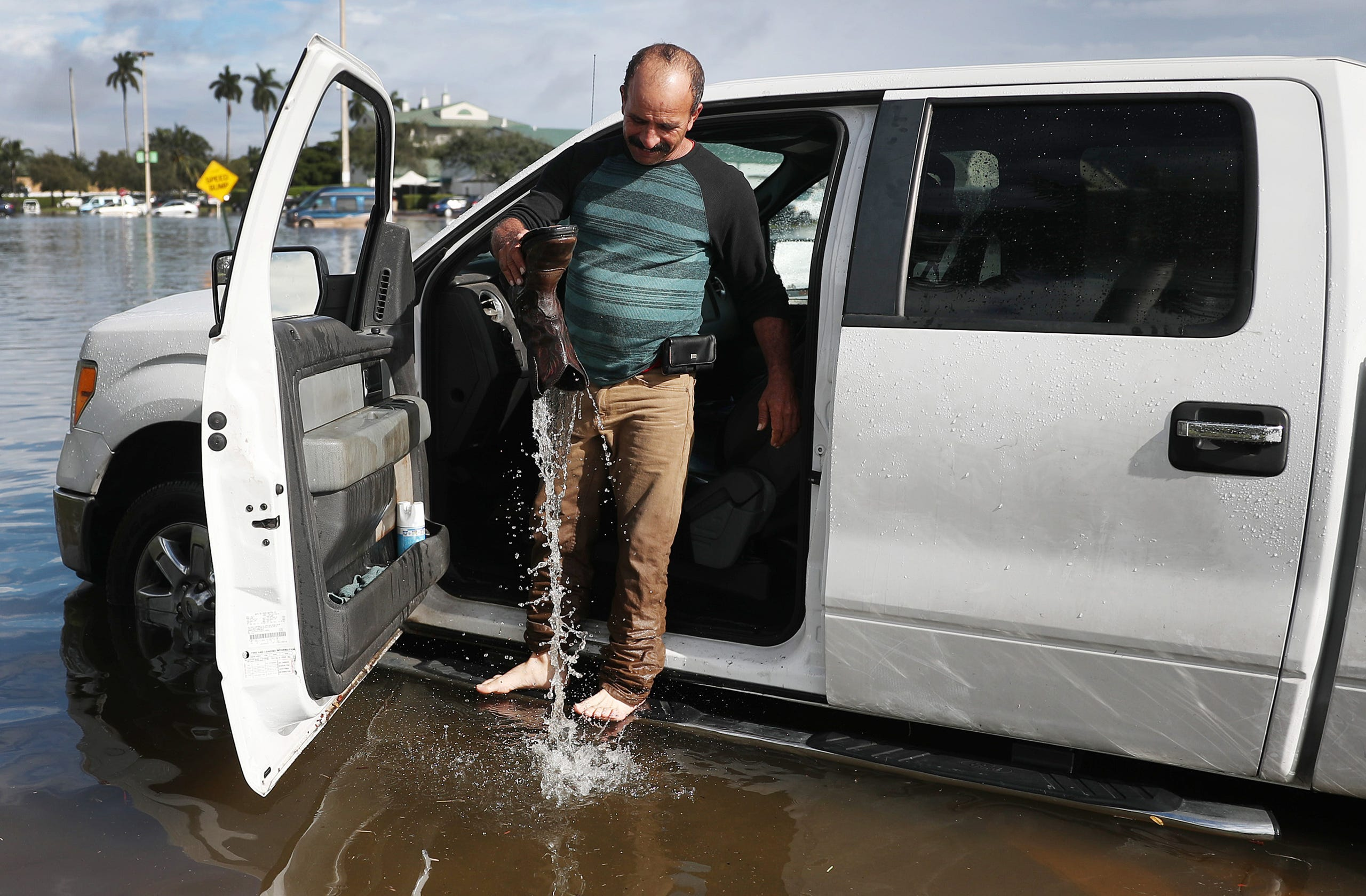 Julio Borges empties his boot of water as he tries get his truck to start after it was inundated with flood waters on Dec. 23, 2019 in Hallandale, Fla.