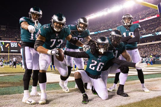 Eagles running back Miles Sanders (26) celebrates his touchdown against the Dallas Cowboys with his Philadelphia teammates during the third quarter.