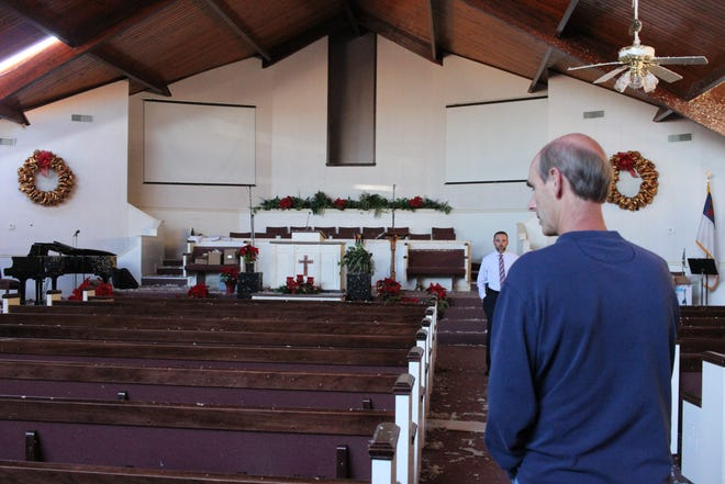 Pastor Rusty Thrift (left) and teacher Mark Poe walk in the main part of Hope Baptist Church on Christmas Eve. Both men were at the church and school on Dec. 16 when an EF-3 tornado hit.