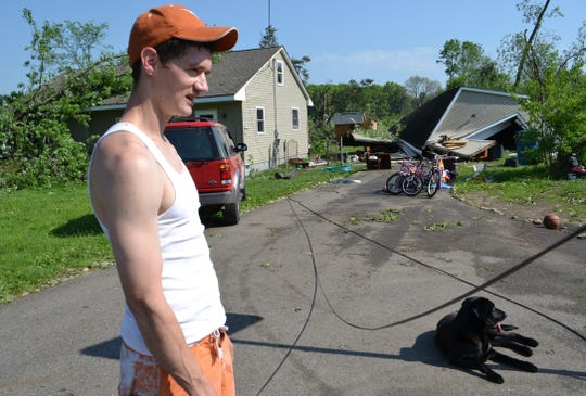 Travis Arney, seen with his family's dog Chloe, outside a rented house on East Michigan Avenue in Emmett Township. The home was damaged in a storm on May 29, 2011.