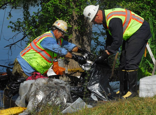 Workers take oil-covered debris from the Kalamazoo River between Kendall and 20th Street along Jackson Street on July 27, 2010.