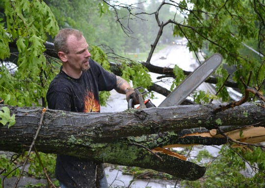 Brian Badger cuts through a downed tree that blocks Capital Avenue Southwest between Hamilton and Minge following a storm on May 29, 2011.