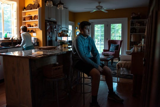 Carlos Sanchez-Snodgrass, 14, sits in his kitchen with his grandma, feeling anxious about a chemotherapy treatment on Thursday, Sept, 26, 2019 in Marshall, Mich. Carlos has B-cell acute lymphoblastic leukemia, a cancer of the bone marrow and other blood-forming tissues.