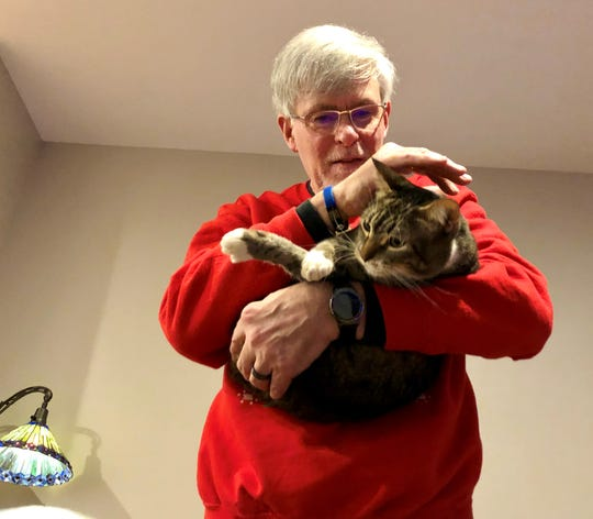 Chuck Crawford pets his cat, Gandolf, at his home in East Bremerton Friday. Gandolf was nearly killed by an infection but survived thanks to the efforts of the Kitsap Humane Society — and Crawford himself, who used laser therapy to help the cat heal.