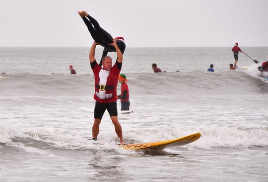 Bear and Cindy Woznick pulled off some tandem surfing. Thousands turned out to watch hundreds of Surfing Santas catch some waves in Cocoa Beach for the 10th annual Surfing Santas event Tuesday morning.