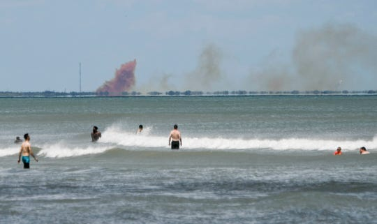 A cloud of orange smoke rises over the Cape as seen from Cocoa Beach.  SpaceX reported an anomaly during test firing of Dragon 2 Saturday afternnon. There are no reported injuries.