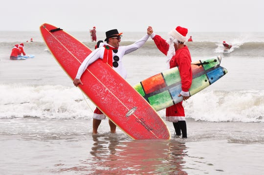 George Trosset Jr. and George Trosset, the two that started it all, high five each other. Thousands turned out to watch hundreds of Surfing Santas catch some waves in Cocoa Beach for the 10th annual Surfing Santas  event Tuesday morning. Ten years ago,  George Trosset, his son George Jr. and his daughter-in-law went surfing in Santa and Christmas costumes behind their house on Christmas Eve.  The event has grown and now raises money for two local nonprofits - Grind for Life, which helps with financial assistance for cancer patients, and the Florida Surf Museum.
